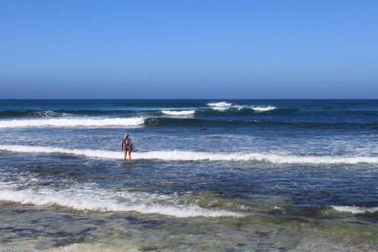 Maman surfeuse avec ces deux surfeurs au loin!