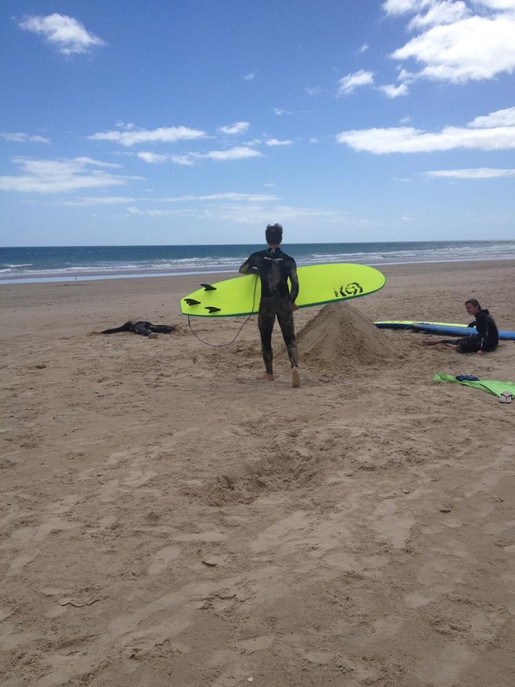 Thomas avec sa planche de surf (et le gros tas de sable de Kilian)